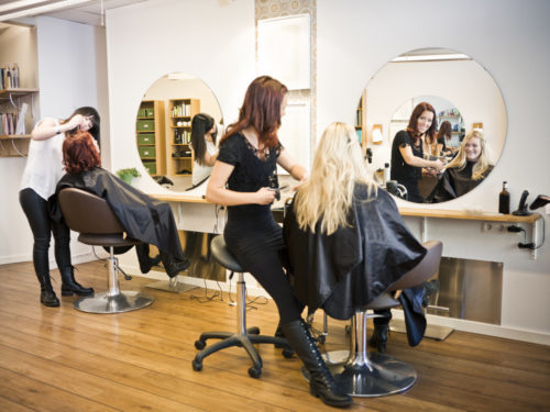 cosmetologist styling blonde woman's hair