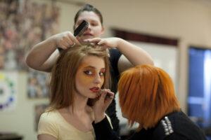 Makeup artists apply yellow makeup to match yellow shirt