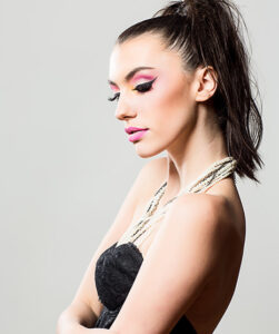 Female model with thick lashes, pink eyeshadow and a tight black dress
