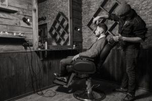 Suit-clad man at classic barber shop having his hair styled