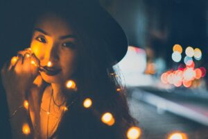 trendy girl in hat holding holiday lights