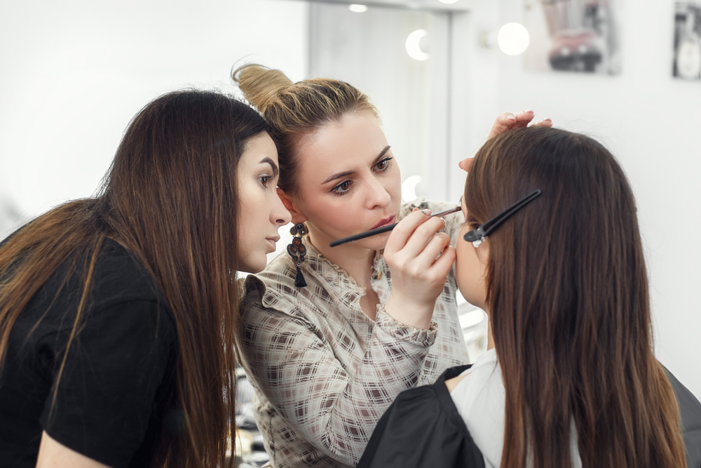 woman watching another woman do a third woman's makeup