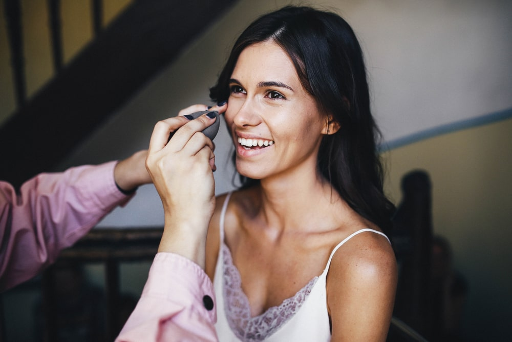 woman getting her makeup done and smiling very happily