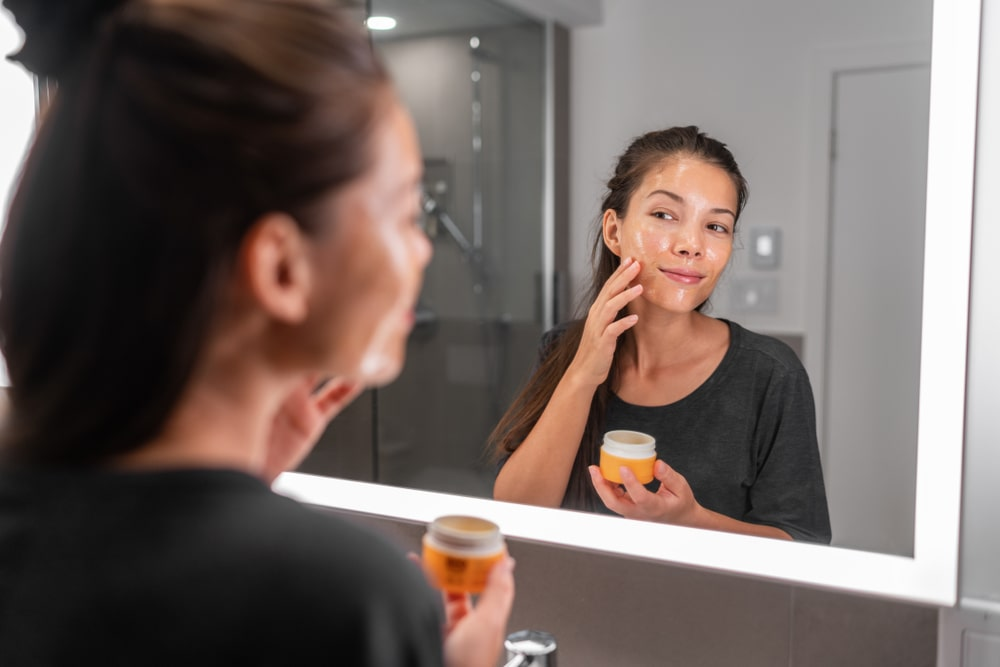 Woman applying something to her face.