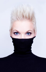 Female model with spiked white hair, captivating blue eyes and an ultra tall turtleneck