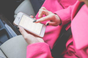 Woman in pink pea coat uses calendar app on iPhone