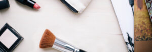 Makeup brush and lipstick upon a table