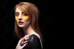 Woman with heavy yellow blush and orange eyeshadow