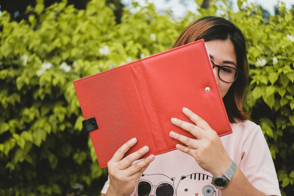 Girl holding up a tablet with a red case.