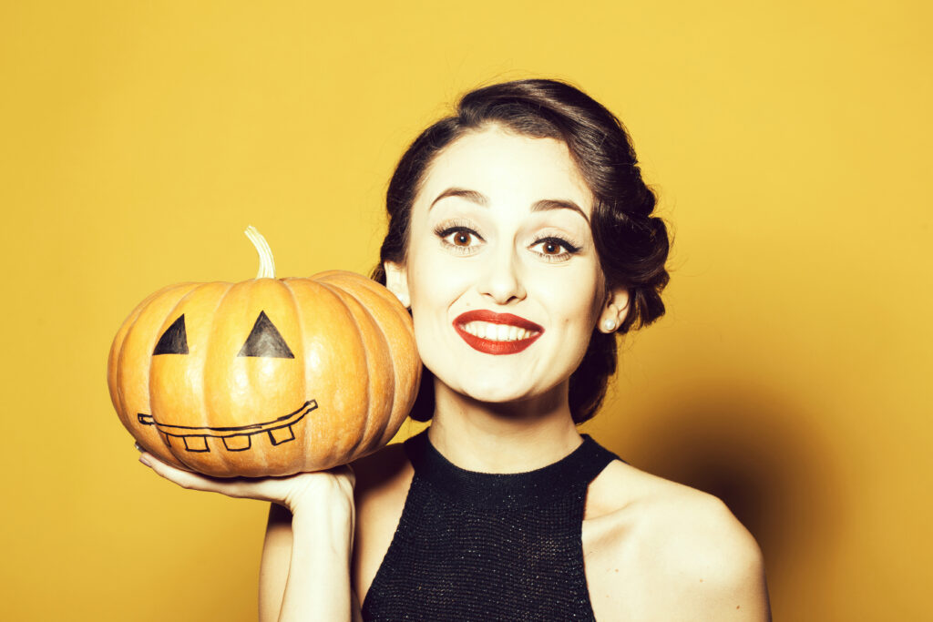 smiling brunette woman in front of yellow wall holding a painted pumpkin