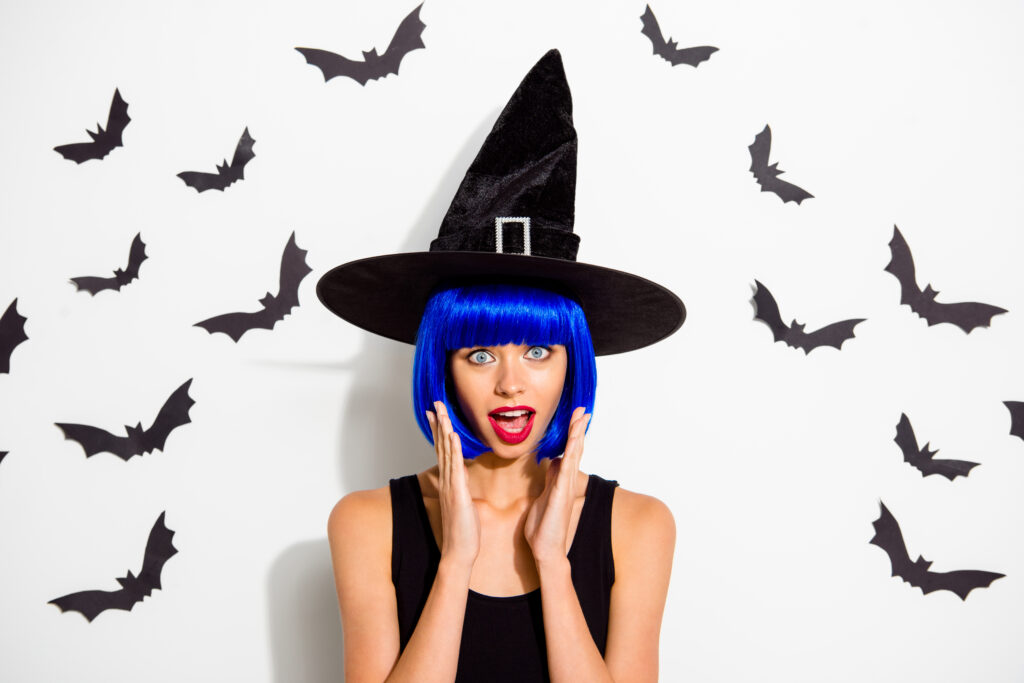 woman with blue hair and witch hat looking surprised in front of white wall with black bats