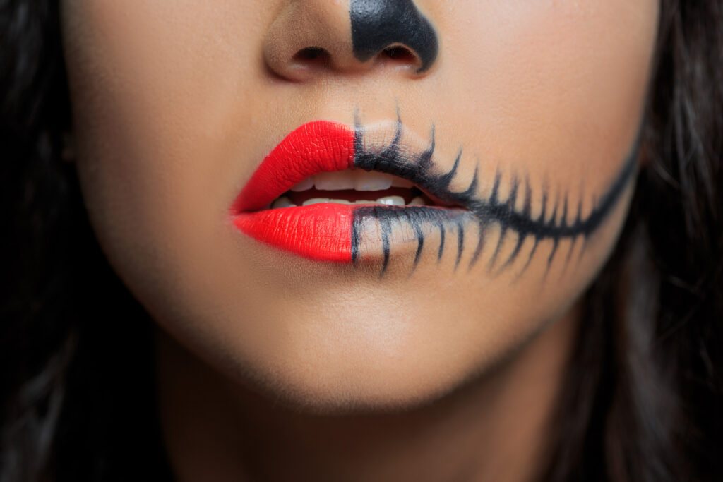 close up of woman's face with half red lipstick and half skeleton makeup