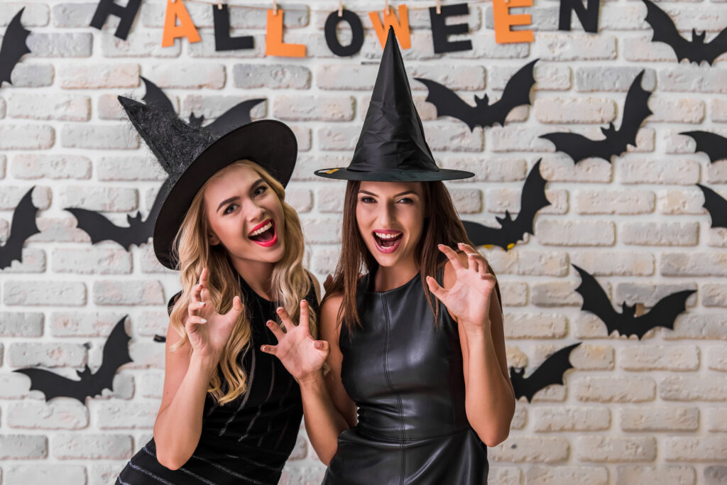 two women wearing witch hats having fun in front of wall with bats and Halloween sign