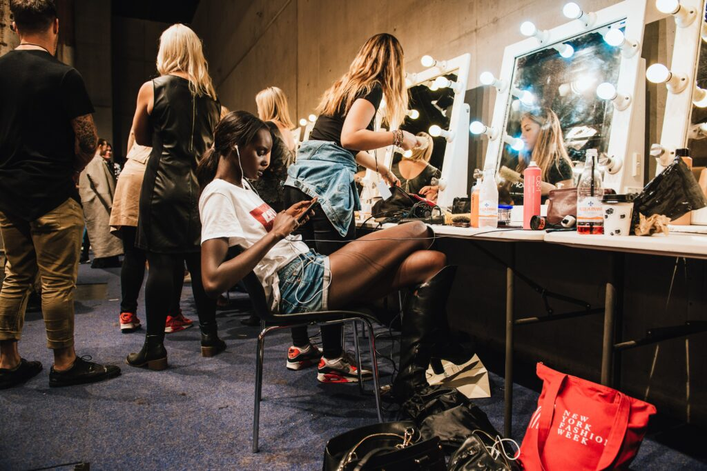 Makeup artists backstage of a runway show with models.