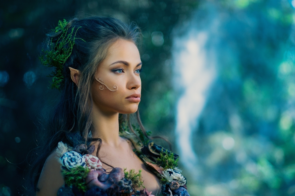 Woman dressed as an elf poses in a forest