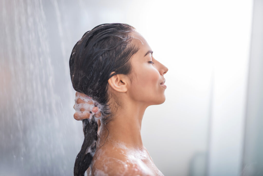 Closeup of young brunette woman washing her hair in the shower