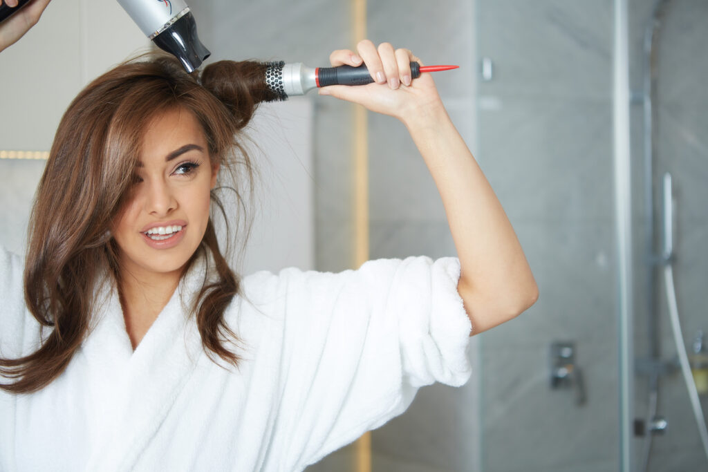 young smiling woman in robe blow drying her hair with a round brush