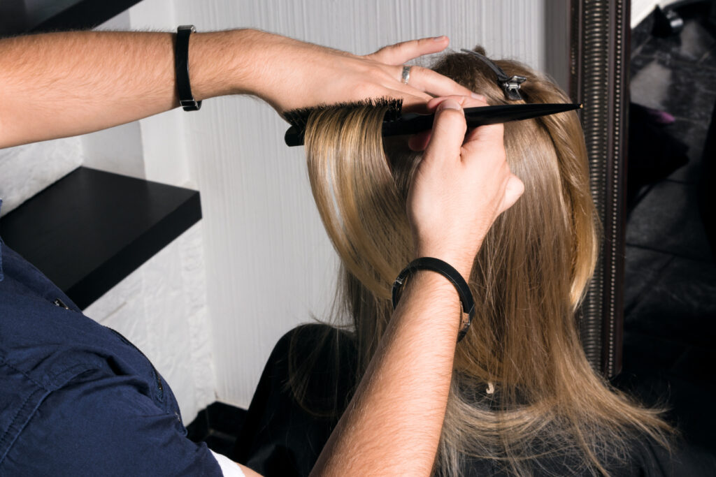 Hands of hairstylist using teasing comb to tease woman's hair