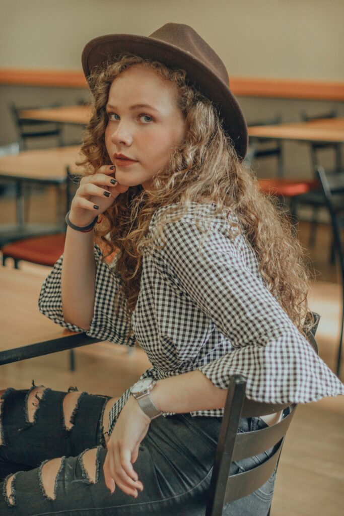 Girl with curly blonde hair in a plaid top sitting in a classroom.