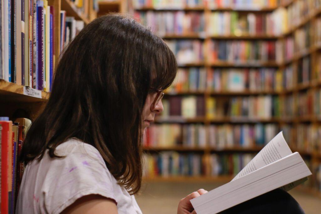 Brunette girl reading in a library.