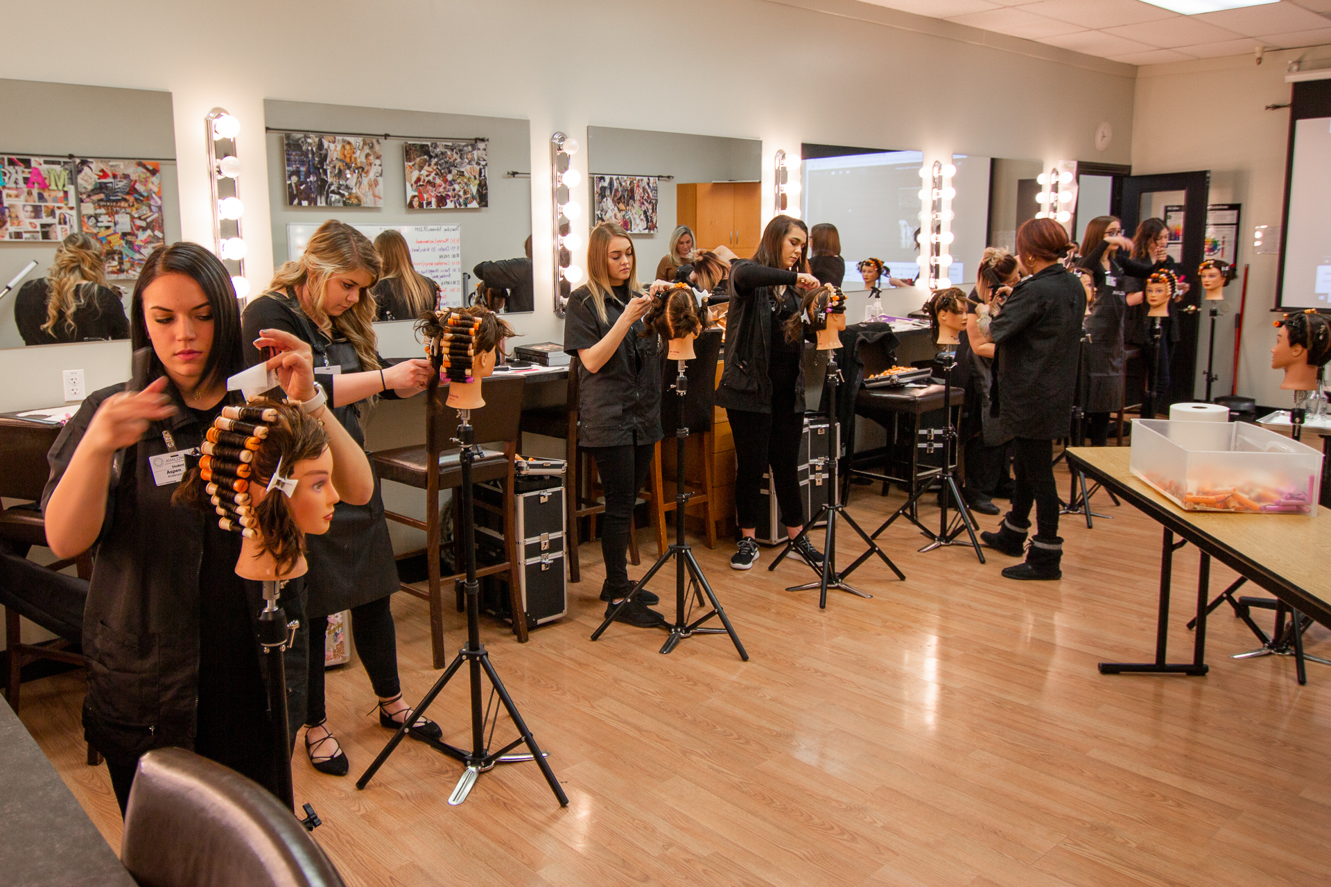 A class of people in beauty school practicing on hair dummies
