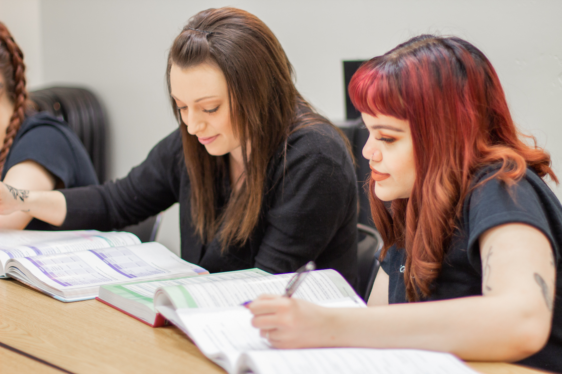 Two women studying together in beauty school