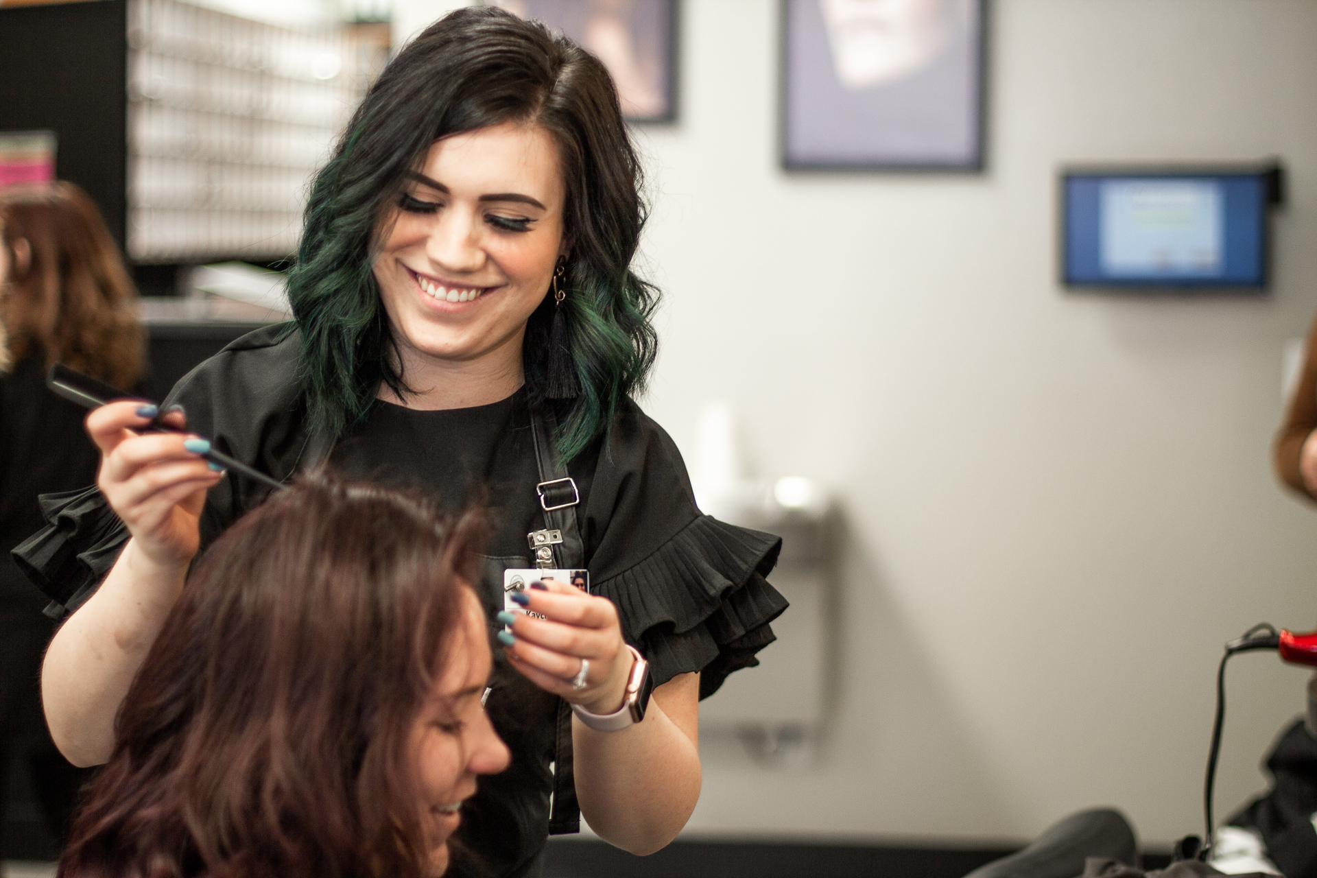 Woman coloring another woman's hair in beauty school
