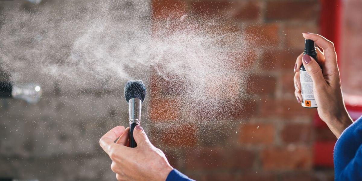 person spraying a makeup brush