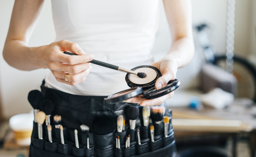 makeup artist with brushes and makeup