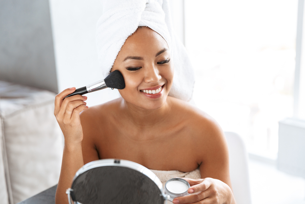 woman looking in the mirror and putting on product with a makeup brush