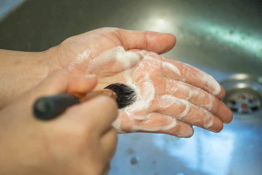 person washing a makeup brush on their hand with soap in the sink