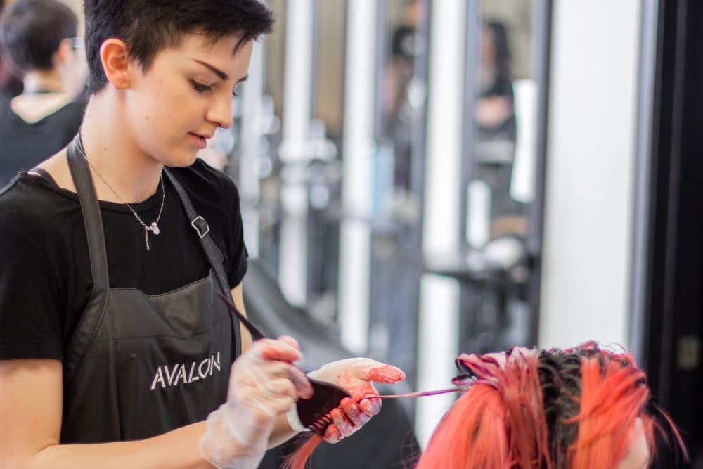 Avalon student adding hair dye to a client under supervision of a licensed professional.