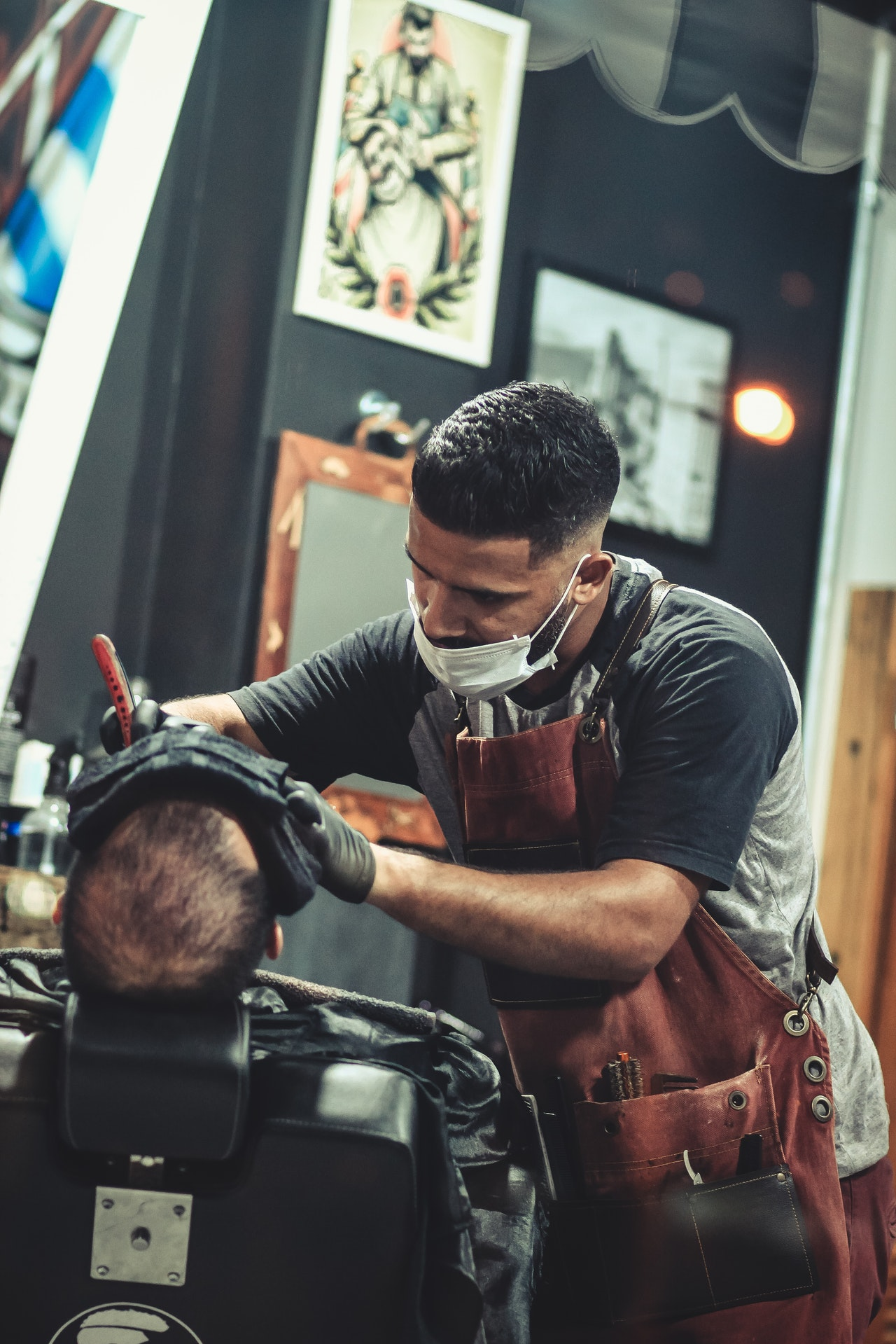 barber with a facemask doing a shave