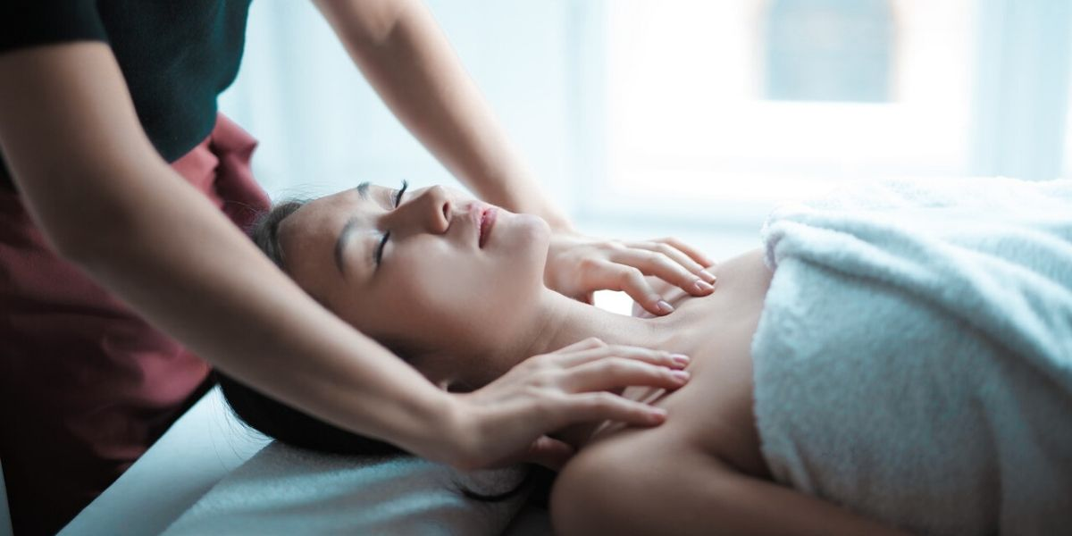 woman laying on back getting a shoulder massage