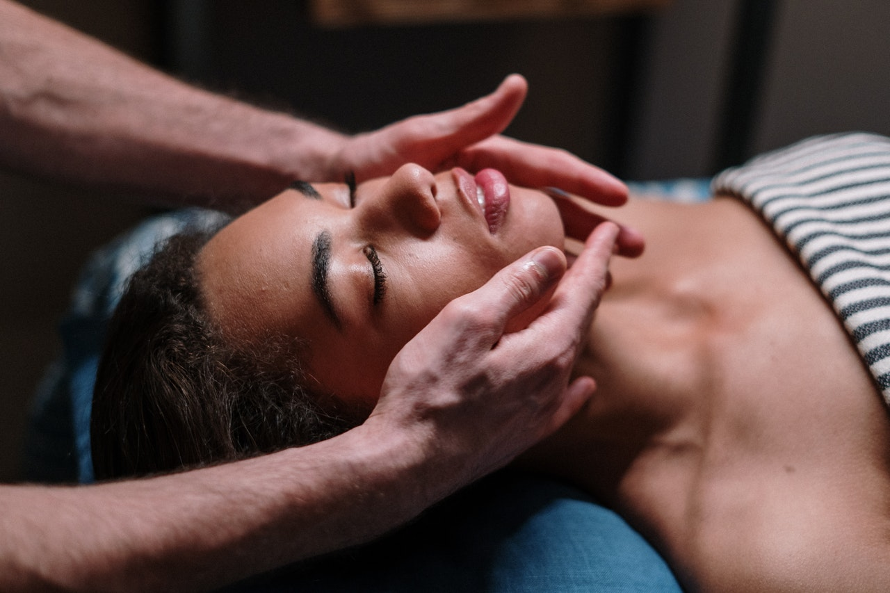 woman on her back getting a facial massage