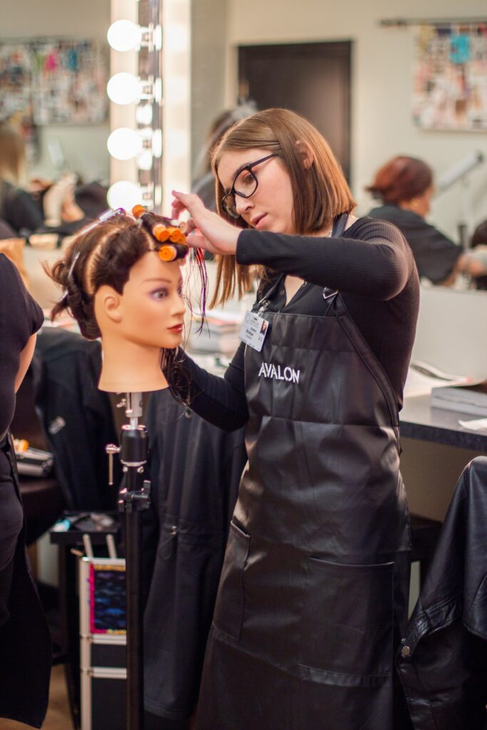 Avalon School of Cosmetology Student applying curls.