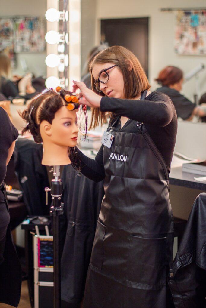 Avalon School of Cosmetology Student applying curls.